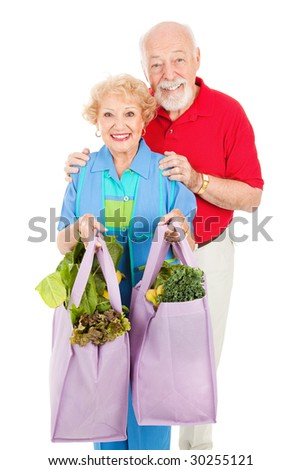 Senior couple using reusable shopping bags to bring home their groceries.  Isolated on white.