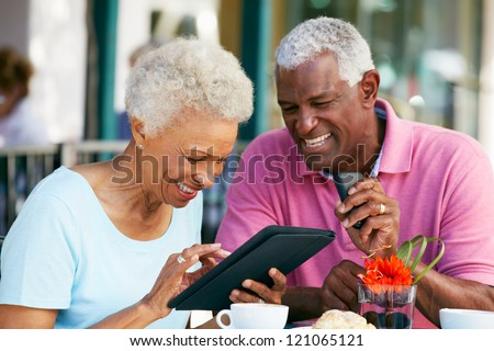 Senior Couple Using Tablet Computer At Outdoor Cafe - stock photo