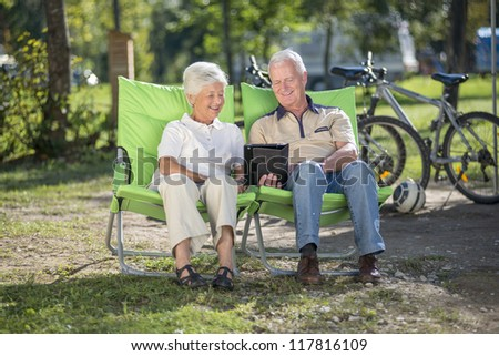 Senior couple using tablet computer while camping - stock photo
