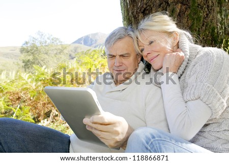 Senior couple using tablet in forest - stock photo