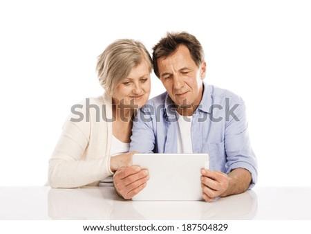 Senior couple using tablet, isolated on white background - stock photo