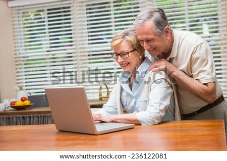 Senior couple using the laptop together at home in the kitchen - stock photo
