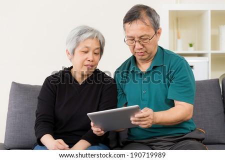 Senior couple using their tablet - stock photo