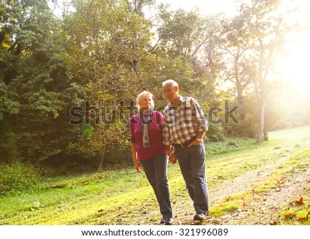 Senior couple walking along autumn path holding each other hands. - stock photo