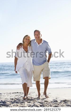 Senior Couple Walking Along Beach - stock photo