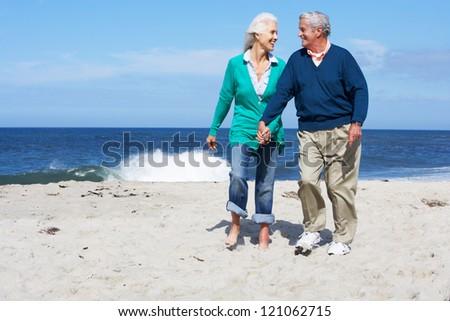 Senior Couple Walking Along Beach Together - stock photo
