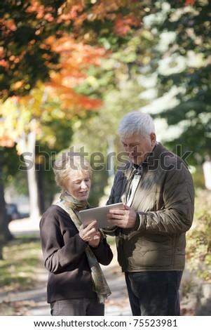 Senior couple walking along the sidewalk looking at their digital tablet - stock photo