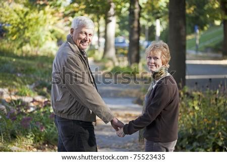 Senior couple walking along the sidewalk looking back at the camera - stock photo