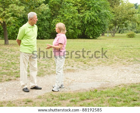 Senior couple walking and speaking in the park. - stock photo