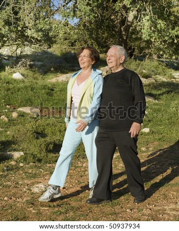 senior couple walking exercise outdoors in woods - stock photo