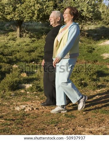 senior couple walking exercise outdoors in woods - stock photo