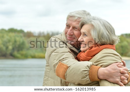Senior couple walking in autumn park - stock photo