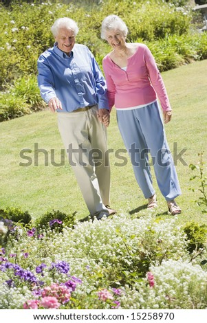 Senior couple walking in garden admiring flowerbeds - stock photo