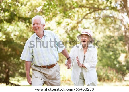 Senior Couple Walking In Park - stock photo