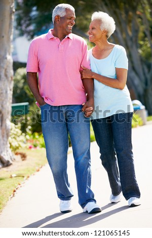 Senior Couple Walking In Park Together - stock photo
