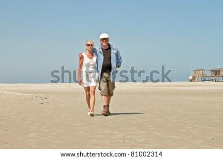 Senior couple walking on empty beach under clear blue sky on hot summer day. - stock photo