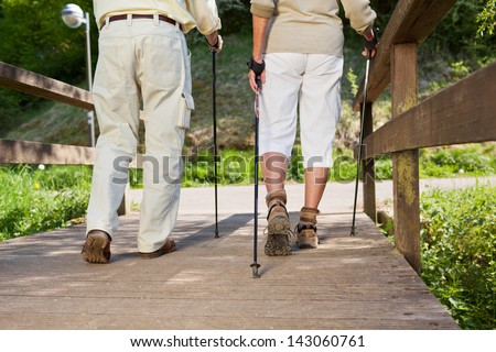 Senior couple walking on the bridge with the help of nordic sticks. - stock photo