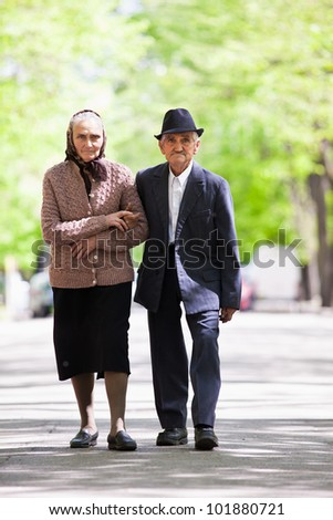 Senior couple walking outdoor in the park - stock photo