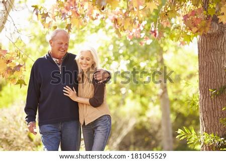 Senior Couple Walking Through Autumn Woodland - stock photo