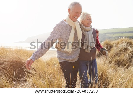 Senior Couple Walking Through Sand Dunes On Winter Beach - stock photo