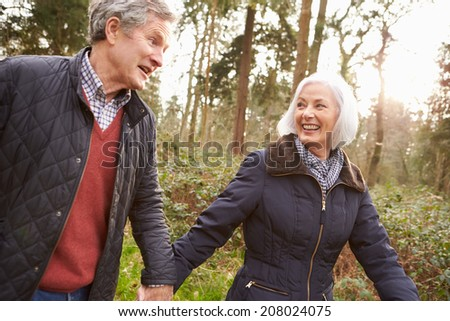 Senior Couple Walking Through Winter Countryside - stock photo