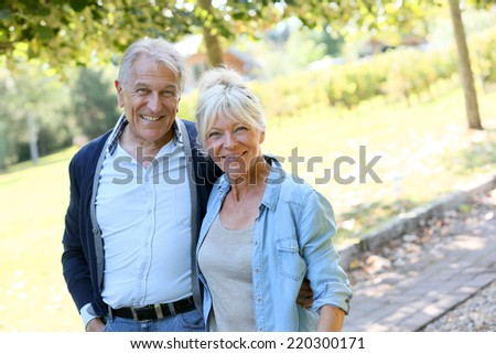 Senior couple walking together in park - stock photo