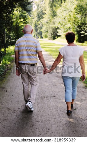 senior couple walking together in summer park