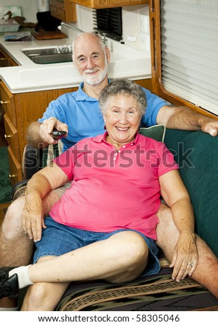 Senior couple watches TV in the cabin of their motor home. - stock photo