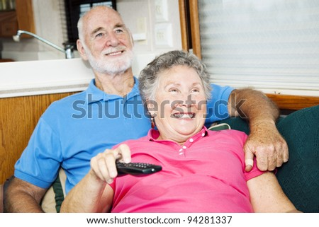 Senior couple watching television in their small traveling motor home. - stock photo