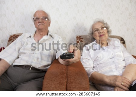Senior couple watching tv. The man uses the remote to change channels - stock photo