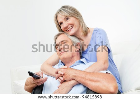 Senior couple watching TV together with remote control at home