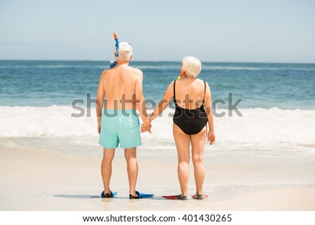 Senior couple wearing flippers on a sunny day - stock photo