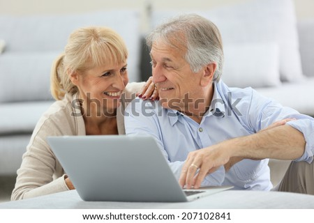 Senior couple websurfing on internet with laptop - stock photo