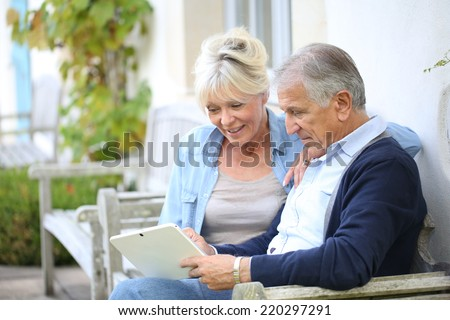 Senior couple websurfing on internet with tablet - stock photo