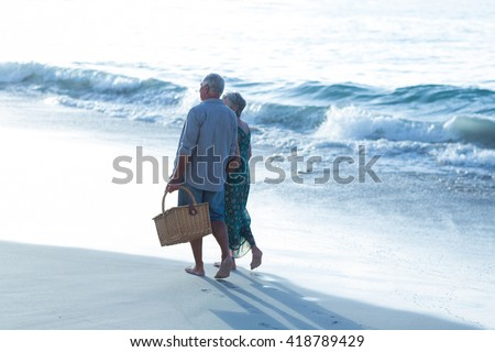Senior couple with a picnic basket at the beach - stock photo