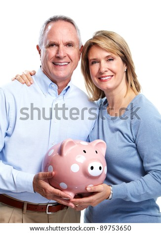 Senior couple with a piggy bank. Isolated on white background. - stock photo