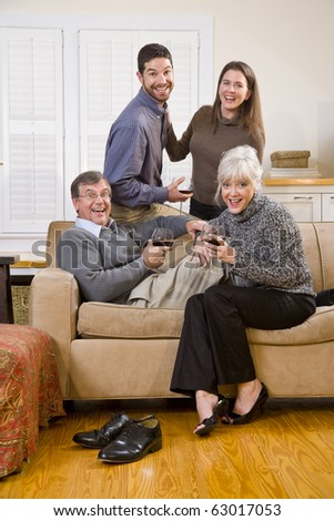 Senior couple with adult children conversing and drinking wine - stock photo