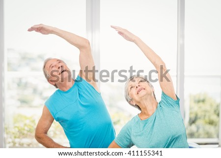 Senior couple with arms raised while exercising at home - stock photo