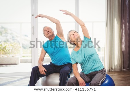Senior couple with arms raised while performing exercise at home - stock photo