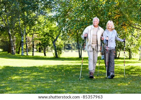 Senior couple with backpacks and trekking poles. Adventure. - stock photo