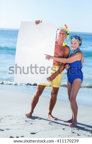 Senior couple with beach equipment holding a white poster at the beach - stock photo