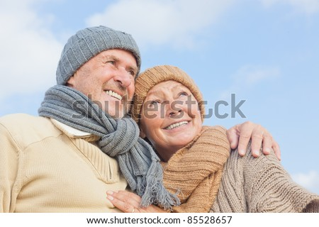 senior couple with blue sky in background having fun in autumn season on the coast in vacation - stock photo