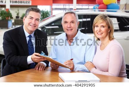 Senior couple with car dealer agent. - stock photo