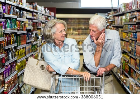 Senior couple with cart at the supermarket - stock photo