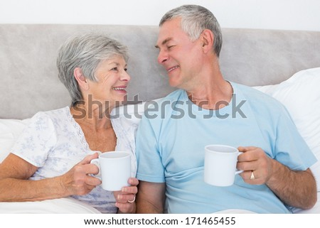 Senior couple with coffee cups while looking at each other in bed at home
