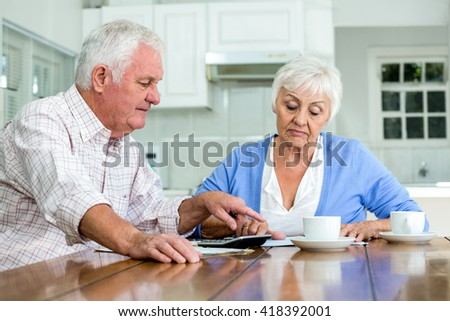 Senior couple with documents while sitting at table in home
