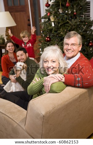 Senior couple with family by Christmas tree - three generations - stock photo
