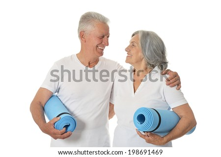 Senior couple with fitness mats On White Background - stock photo