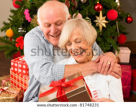 Senior couple with gifts in front of Christmas tree - stock photo
