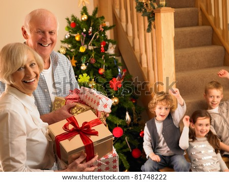 Senior couple with grandchildren at Christmas - stock photo